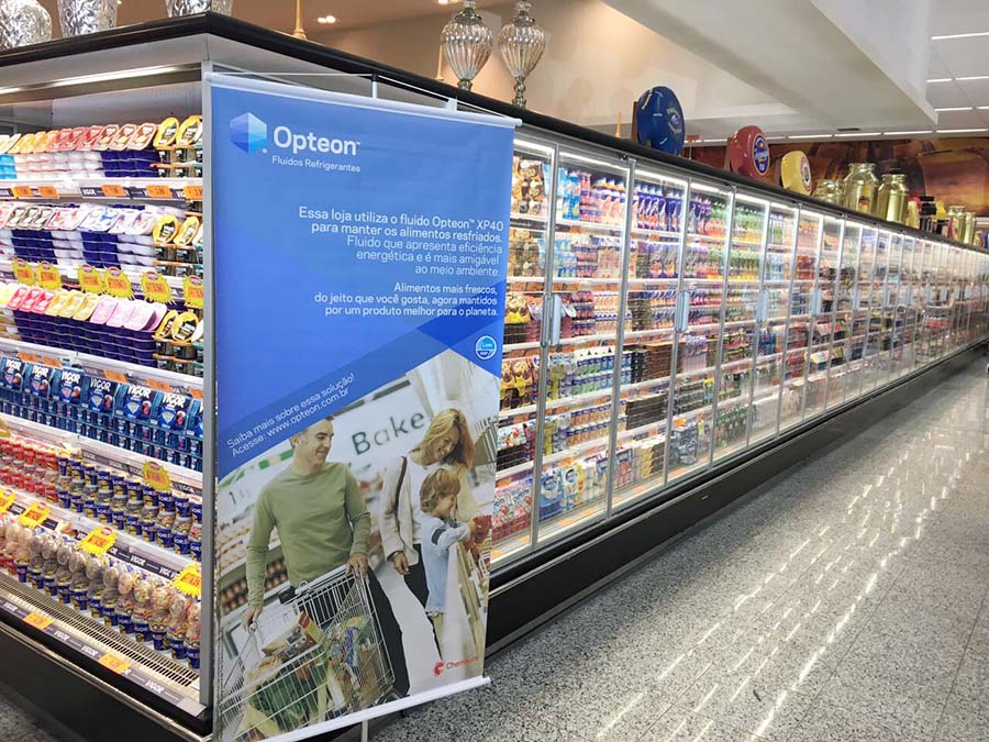 Banner de divulgação do fluido refrigerante Opteon XP40 na área de produtos refrigerados de loja da rede de supemercados Jaú Serve